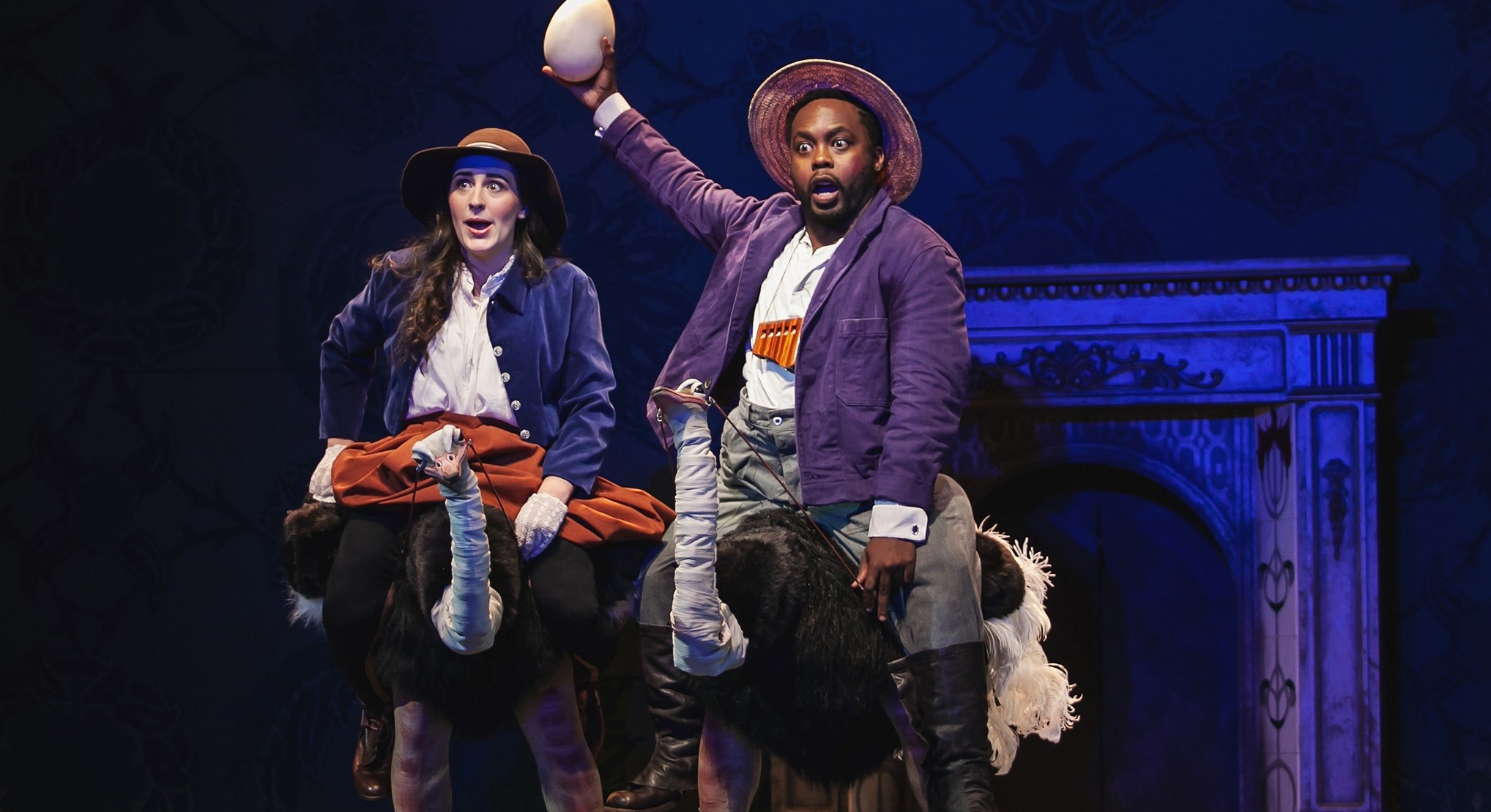 Two opera singers ride ostriches. One is holding up an ostrich egg with a surprised look on his face.