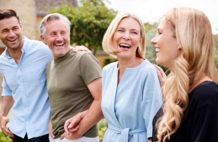 A son, father, mother, and daughter laughing